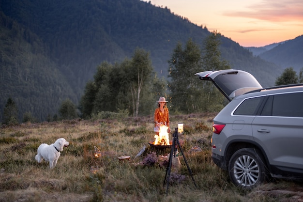 Femme et chien au pique-nique dans les montagnes