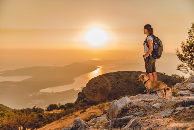 Femme avec un chien au sommet d'une montagne