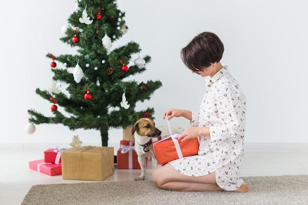 Femme avec chien ouvrant des cadeaux de noël