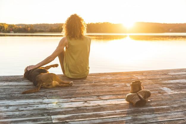 Femme et chien se détendre sur le quai au coucher du soleil