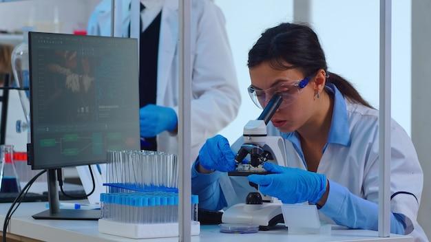 Femme chimiste ajustant des échantillons dans une boîte de pétri et examinant au microscope dans un laboratoire moderne équipé. des trucs multiethniques analysant l'évolution des vaccins à l'aide de la haute technologie pour la recherche de traitements