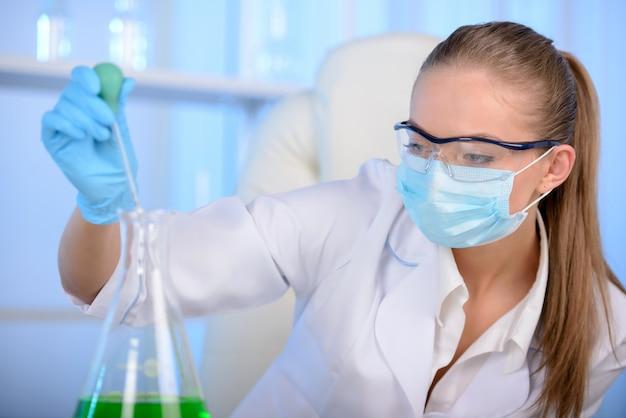 Femme chimiste teste un échantillon de liquide en laboratoire.