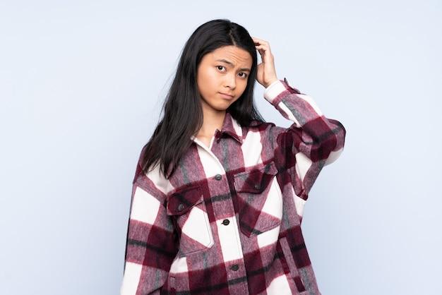 Femme chinoise adolescente isolée sur bleu avec une expression de frustration et de ne pas comprendre