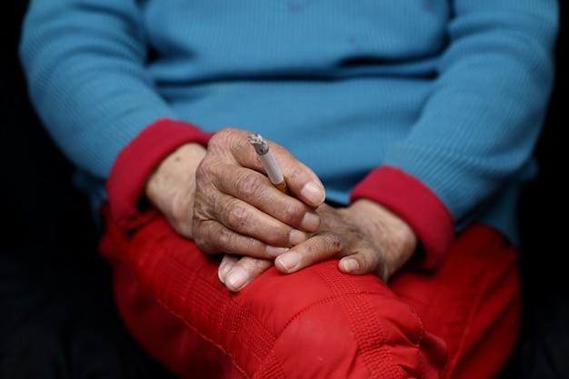 Femme chinoise âgée assise et tabagisme - concept d'autonomisation des femmes