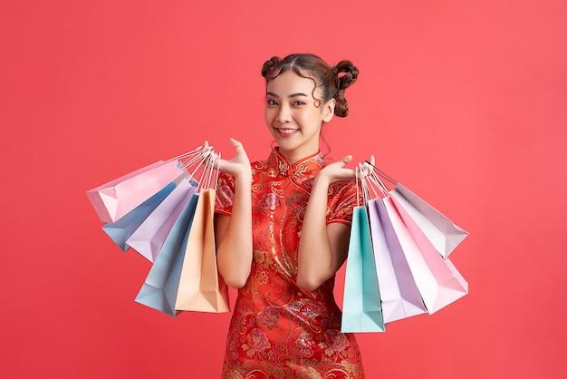 Femme chinoise asiatique en costume traditionnel sur fond rouge avec des sacs à provisions. fête du nouvel an chinois.