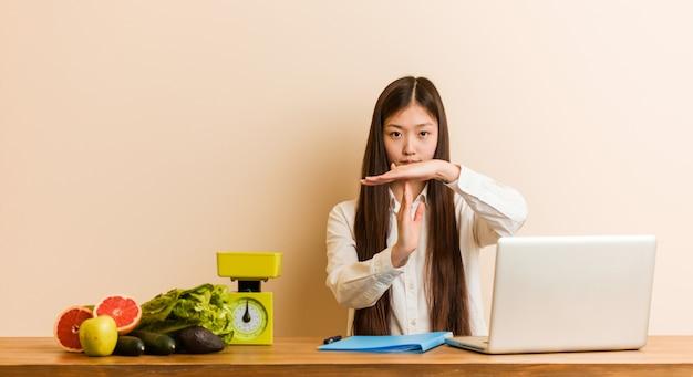 Femme chinoise jeune nutritionniste travaillant avec son ordinateur portable, montrant un geste de délai d'attente.