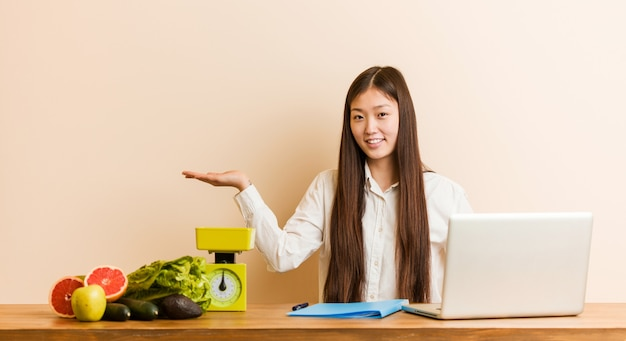 Femme chinoise jeune nutritionniste travaillant avec son ordinateur portable