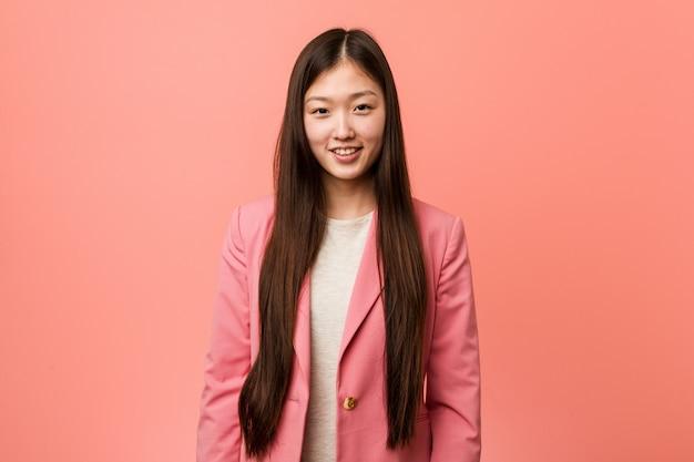 Femme chinoise de jeunes entrepreneurs portant le costume rose heureux, souriant et gai.