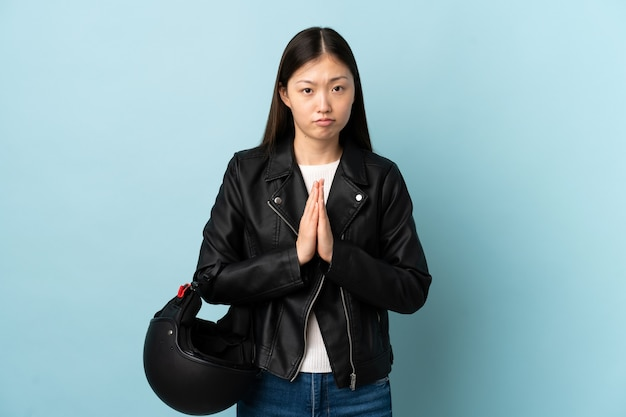 Femme chinoise tenant un casque de moto sur mur bleu isolé plaidant