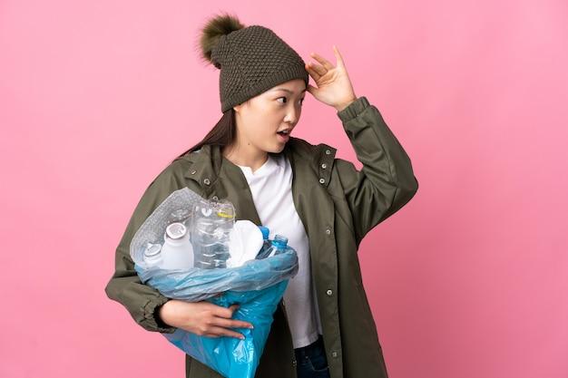 Femme chinoise tenant un sac plein de bouteilles en plastique à recycler sur rose isolé avec une expression de surprise tout en regardant côté