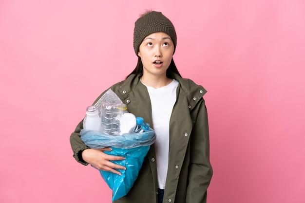 Femme chinoise tenant un sac plein de bouteilles en plastique à recycler sur rose isolé à la recherche et avec une expression surprise