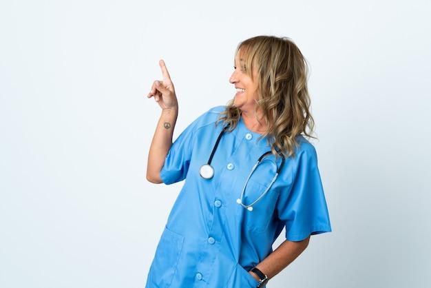 Femme chirurgien d'âge moyen sur fond isolé pointant vers une excellente idée