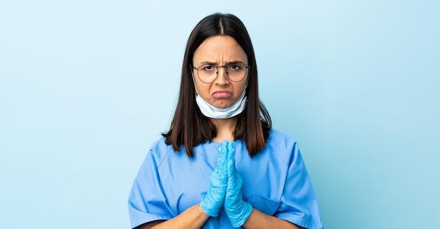 Femme chirurgien sur le mur bleu maintient la paume ensemble.