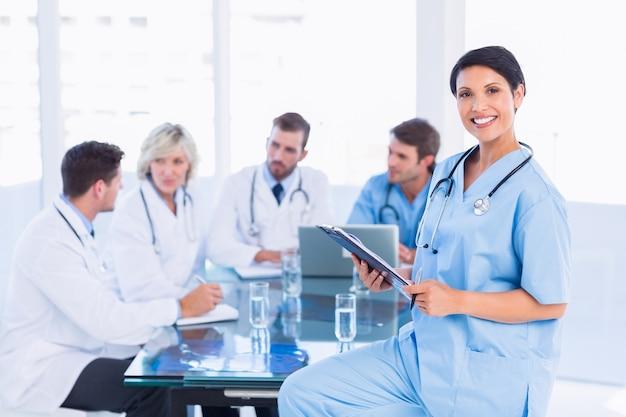 Femme chirurgien tenant des rapports avec des collègues en réunion
