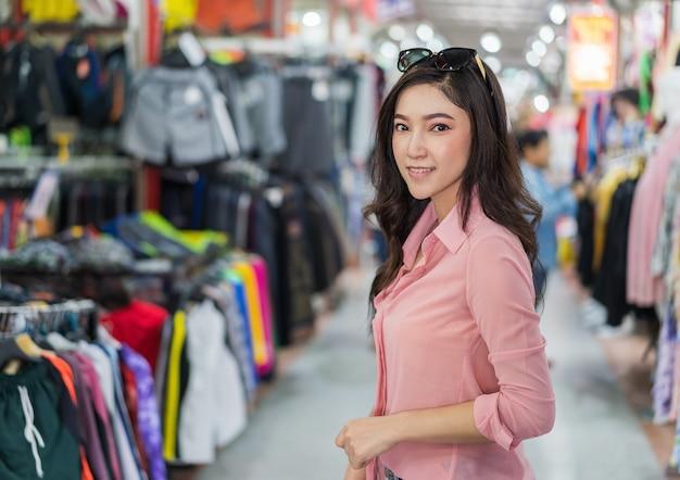 Femme choisissant et achetant des vêtements dans une boutique