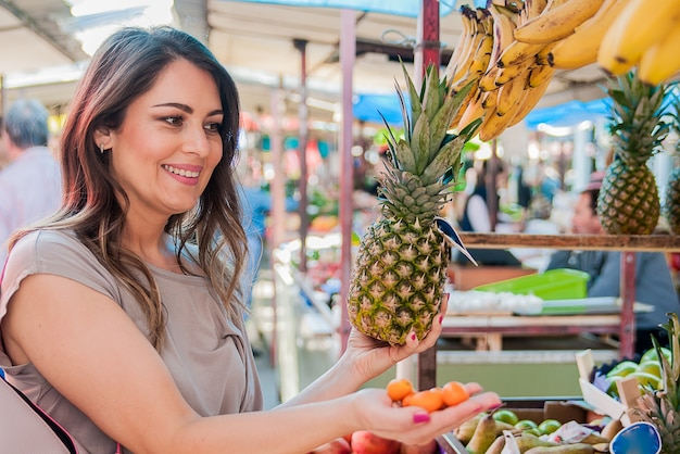 Femme choisissant l'ananas au cours du shopping sur le marché vert des légumes-fruits. attractive femme shopping. belle jeune femme ramassant, choisissant des fruits, des ananas.