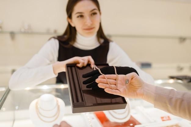 Femme choisissant chaîne en or en bijouterie