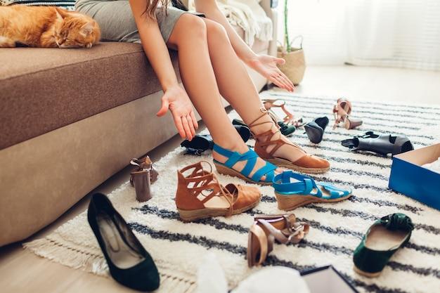 Femme choisissant des chaussures et les essayant à la maison. choix difficile à faire avec des sandales, des talons et des chaussures plates