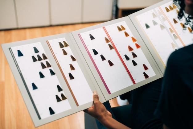 Femme choisissant la couleur des cheveux dans le catalogue de teinture