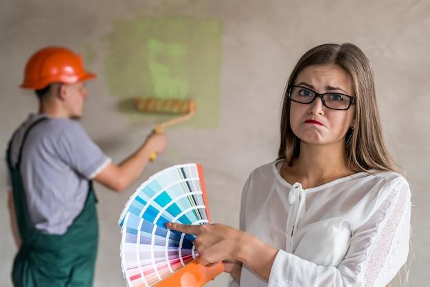 Femme choisissant la couleur pour peindre les murs dans l'appartement