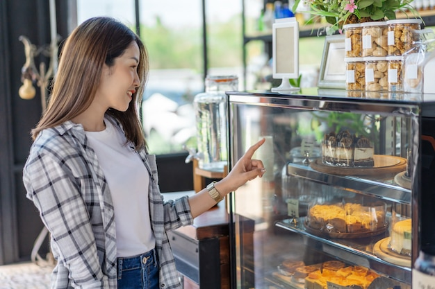 Femme choisissant un gâteau dans un café