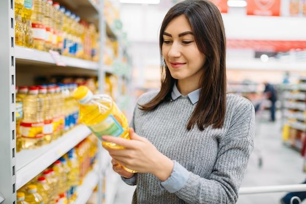 Femme choisissant l'huile de tournesol dans un supermarché, shopping familial. cliente en magasin, acheteur sur le marché