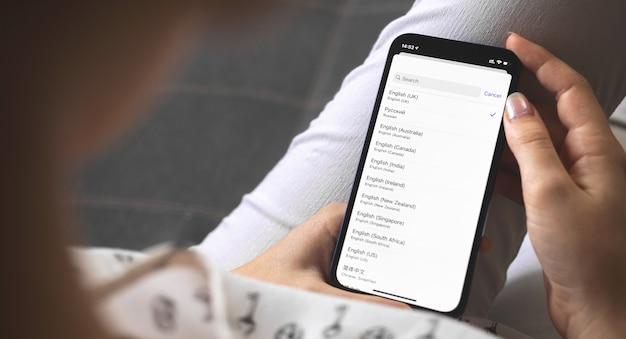 Femme choisissant la langue sur son nouveau téléphone portable, paramètres de langue sur les smartphones