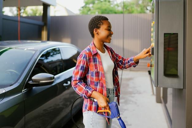 Femme choisissant le programme sur la station de lavage de voiture