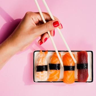 Femme choisissant un sushi dans une assiette