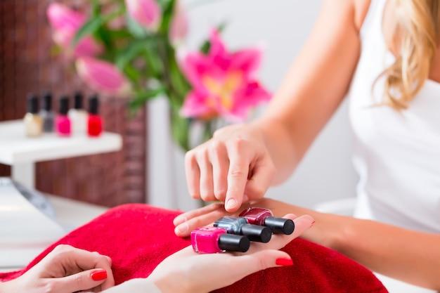 Femme choisissant un vernis à ongles dans un institut de beauté