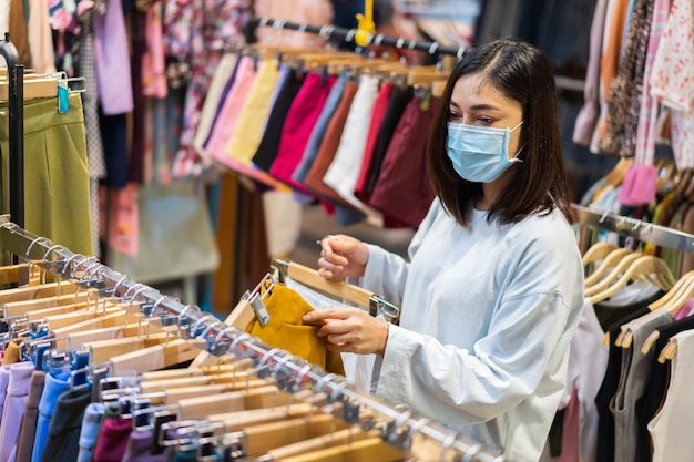 Femme choisissant des vêtements au centre commercial et portant un masque médical pour la prévention du coronavirus