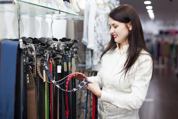Femme choisit la ceinture au magasin