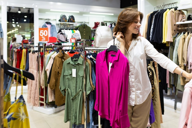 La femme choisit une chemise d'été lumineuse dans un magasin de vêtements.