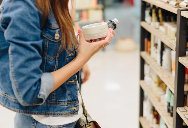 Une femme choisit des cosmétiques dans un magasin