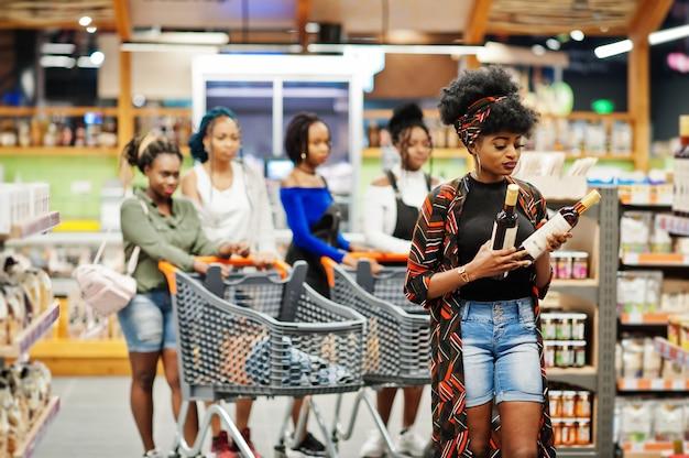 Femme choisit du vin au supermarché contre ses amis afro avec panier d'achat