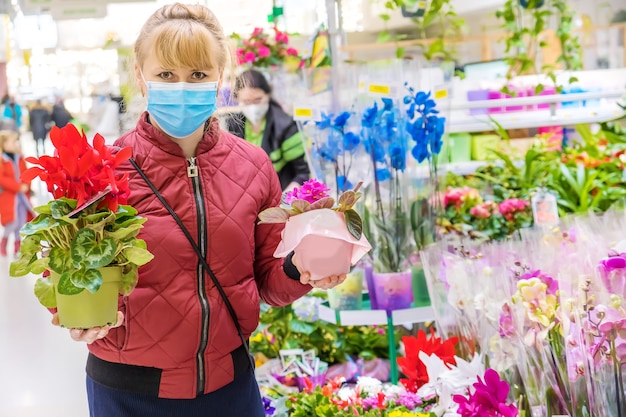 Une femme choisit une fleur dans un pot de fleurs dans un magasin de fleurs