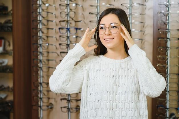 La femme choisit des lunettes dans le magasin.