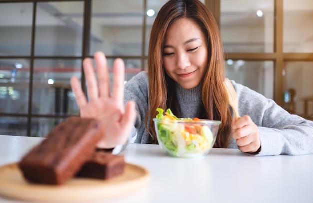 Une femme choisit de manger une salade de légumes et fait signe à la main de refuser un gâteau au brownie sur la table