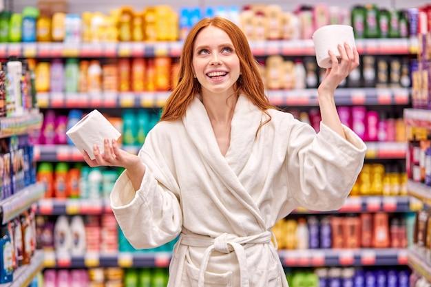 La femme choisit le meilleur papier toilette en magasin, vêtue d'un peignoir blanc, s'amuse dans l'allée du supermarché