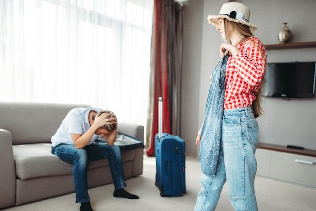 Une femme choisit une robe lors d'un voyage contre un mari fatigué