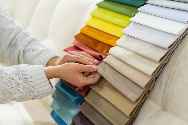 La femme choisit le tissu sur le canapé