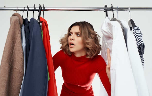 La femme choisit des vêtements dans un magasin à la mode et un style de garde-robe