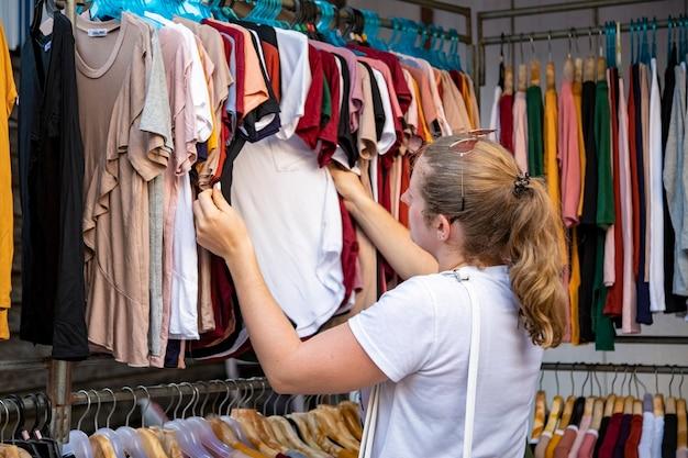 La femme choisit des vêtements en passant par le diffuseur dans le magasin du marché. vue arrière