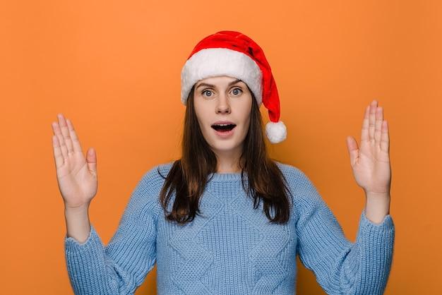 Femme choquée au chapeau montre quelque chose de grand et de grande taille