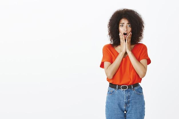 Femme choquée avec une coiffure afro posant en studio