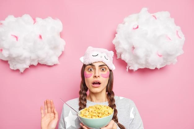 Une femme choquée embarrassée avec deux nattes garde la bouche ouverte réagit à quelque chose de génial tient un bol de cornflakes vêtus de vêtements de nuit