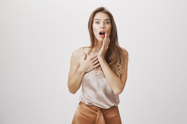 Femme choquée haletante, toucher la joue et regarder la caméra