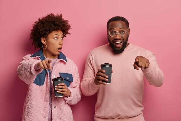 Femme choquée et homme heureux pointent la caméra, remarquez quelque chose d'incroyable, buvez du café dans des gobelets jetables, portez une tenue élégante, exprimez différentes émotions