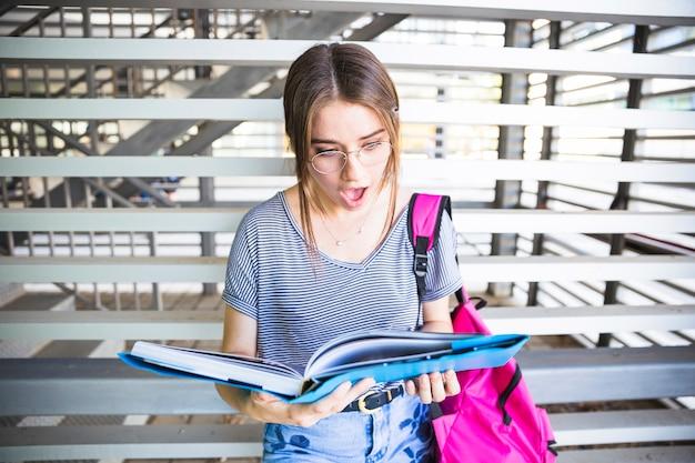 Femme choquée à lunettes en lisant un manuel