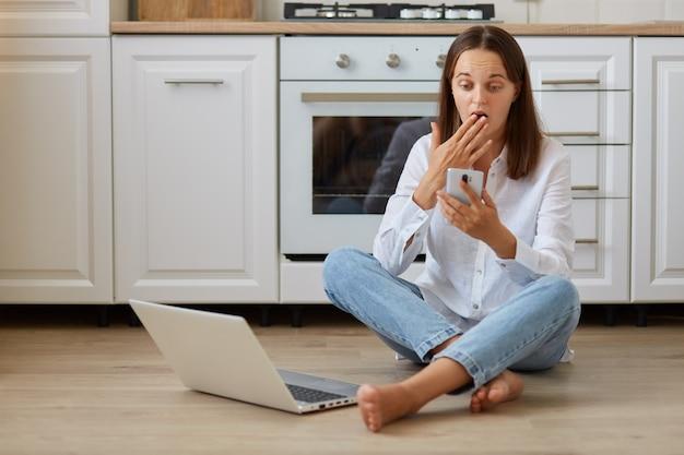 Femme choquée portant une chemise blanche et un jean, assise sur le sol dans la cuisine près d'un ordinateur portable, tenant un téléphone intelligent dans les mains, regardant l'écran de l'appareil avec une expression surprise, couvrant la bouche avec la paume.